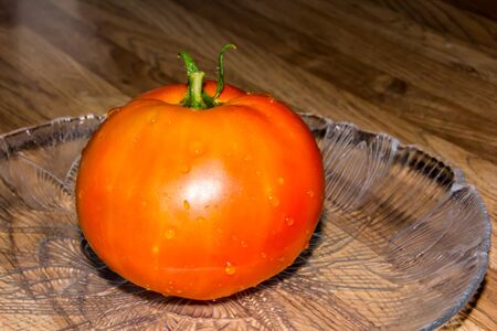 meaty: Tomato on a glass plate on a wooden table