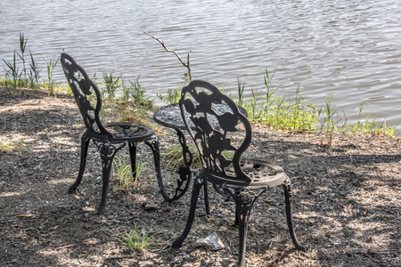 Two wrought iron chairs and table by a lake in Dover, Delaware Фото со стока - 70724687