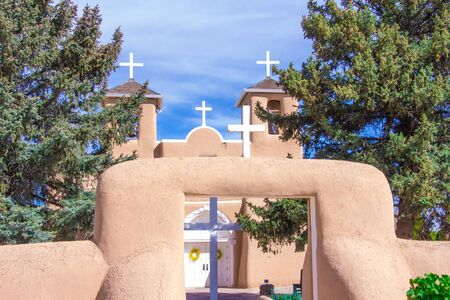 Four White crosses and an adobe church  and wall Фото со стока - 73186091