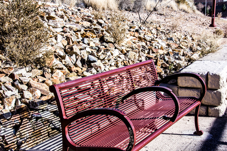 Park bench along a stoney desert hillside. Фото со стока - 76075289
