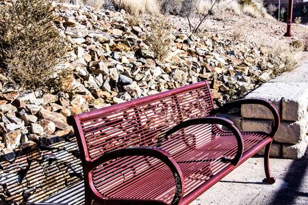Park bench along a stoney desert hillside. Фото со стока