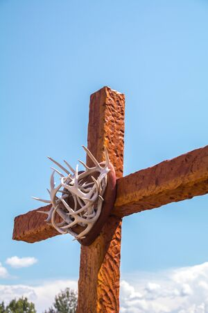 A wooden cross and crown of thorns pointing up to heaven Фото со стока