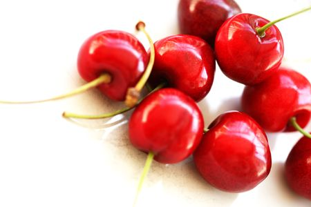 A horizontal colour photograph of red cherries with stems.