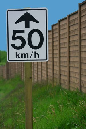 kilometres: A vertical colour photograph of a 50 kmh street sign in front of green grass, a brown fence, and blue sky.