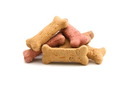 A horizontal color photograph of a pile of dog biscuits over a white background.
