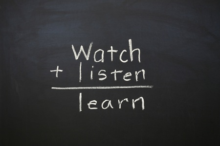 addition symbol: A horizontal color photograph of the statement Watch Listen and Learn written on a chalkboard.