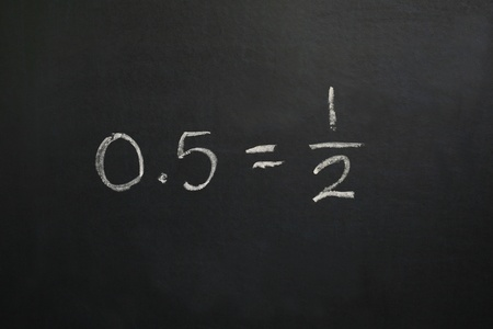 equals: A horizontal color photograph of a blackboard showing the equation zero point five equals one half. Stock Photo