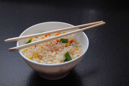 Three delicious Chinese rice with prawns, green beans, corn and carrots, served in a white bowl on which there are two chopsticks. Imagens