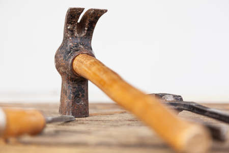 A carpenter's hammer on a table. The hammer head is in focus, the rest is out of focus. There are also other tools such as pliers and a chisel