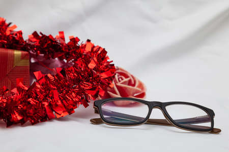 Some glasses next to a decorative red heart, which cannot be seen whole, a gift and a flower. In the background there is a white cloth.