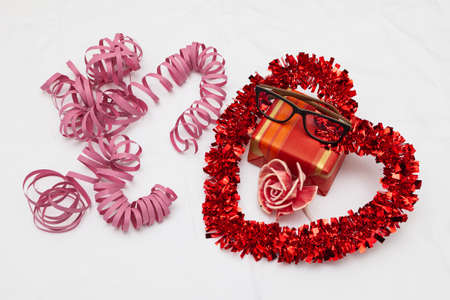 A decorative red heart, a gift, a pink flower and pink streamer ribbons on a white fabric as a background. On top of the gift is a pair of glasses.