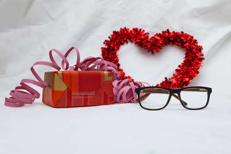 A pair of glasses with a decorative red heart, a gift, a pink streamer and a flower. In the background there is a white cloth. Zdjęcie Seryjne