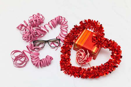 A decorative red heart, a gift, a pink flower and pink streamer ribbons on a white fabric as a background. Next to the streamer is a pair of glasses.