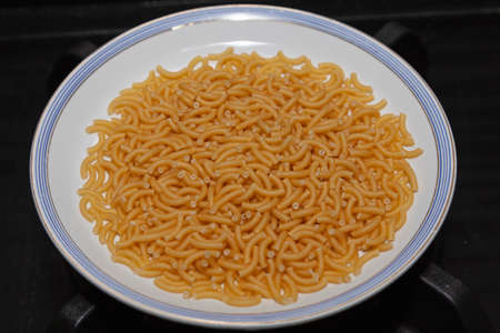 Raw fat noodles prepared on a small plate to make fideua, a typical recipe from the Valencian Community in Spain