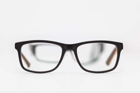 Two pairs of eyeglasses placed on a white surface. The closest ones are in focus and the others are seen through the first ones and are out of focus. The background is white.