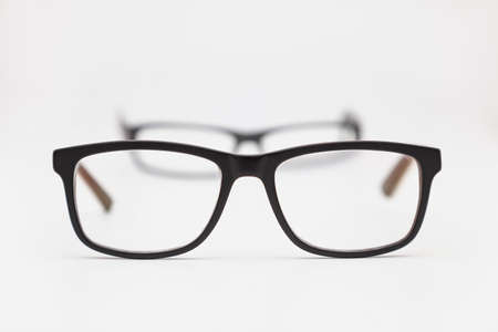Two pairs of eyeglasses placed on a white surface. The closest ones are in focus and the others are out of focus. The background is white.