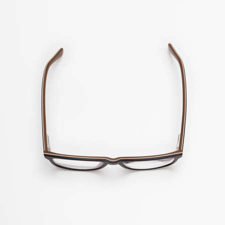 A pair of dark blue and brown eyeglasses with open temples placed on a white surface, viewed from above