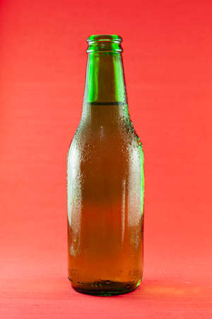 Green glass bottle containing fresh beer with drops of condensation. The background is red. Foto de archivo