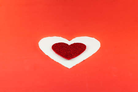 On a red background there is a white cardboard heart and inside it there is a smaller red glitter heart. For Valentine.