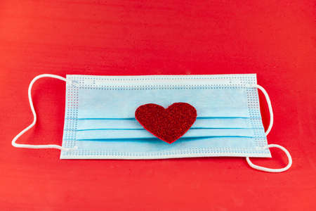 Blue surgical mask with a red glitter heart on top. The objects are placed on a red background. Foto de archivo