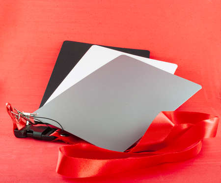 Gray cards for photographers placed on a red background. There are three cards, one gray, one white and one black. They are attached with a hook and a red ribbon. Foto de archivo