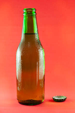 Green glass bottle containing fresh beer with drops of condensation, there is also the cap. The background is red.