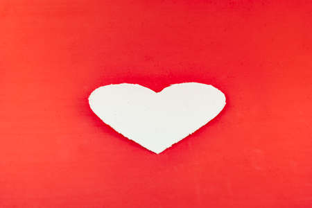 On a red background is a white cardboard heart. For Valentine.