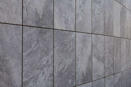 Curved wall located on a street corner with textured gray tiles. The joints between tiles are black and are very marked.