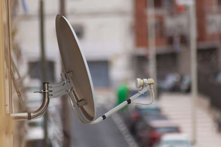 White satellite dish installed on the facade of a building in a town or city. The antenna is in focus and the street is out of focus in the background.