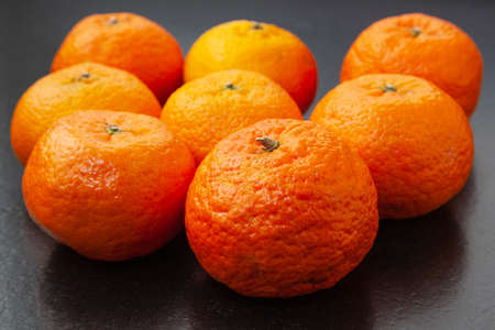 Eight orange tangerines on a black granite bench. Those in the foreground are in focus, and those in the back are out of focus.