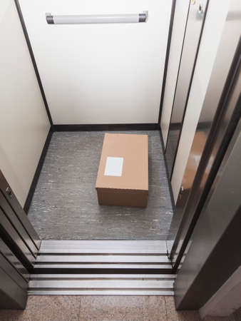 A package delivered to its recipient by leaving it in the elevator to avoid physical proximity in order to prevent the spread of COVID-19. The label is blank for personalization. Foto de archivo