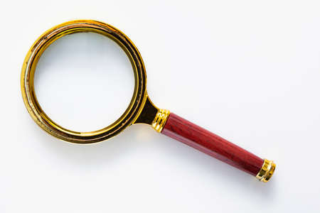 Golden magnifying glass with the plastic handle imitating wood isolated on a white background.