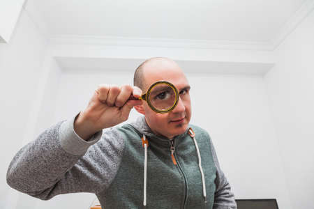 A bald young boy looking through a magnifying glass so that his very large eye is visible. He is wearing a green and gray sweatshirt and is in an office where part of a computer screen is visible. Фото со стока