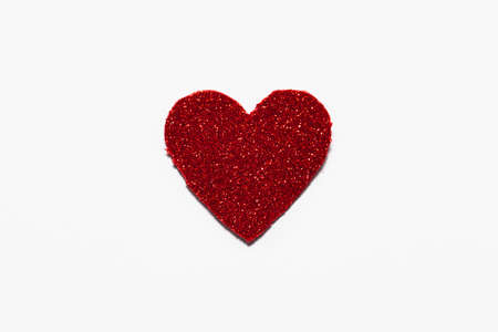 Red glitter heart on white background with space for text in which you can make a Valentine's greeting.