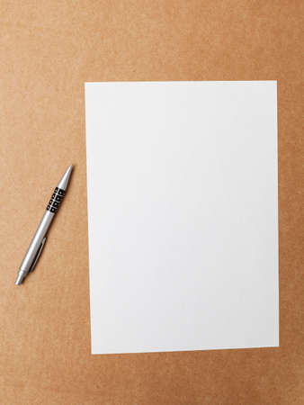 Ballpoint pen and blank sheet of paper on a cardboard surface. The content of the sheet can be fully customized and any text can be written or a drawing can be made.
