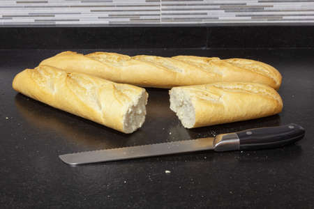 Two loaves of bread on a black granite bench in a kitchen. One of the bars is cut and next to it is the knife with which it was cut. You can see a little bit of the wall tiles.