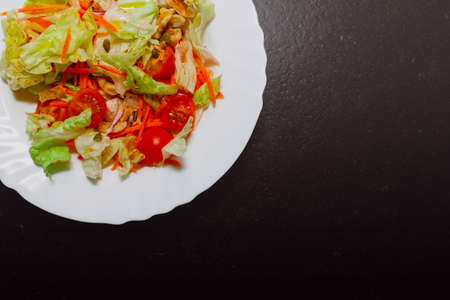 There is a salad plate in a corner of the picture, part of the plate is hidden. The ingredients are: lettuce, cherry tomato, carrot, walnuts, and pumpkin and sunflower seeds. There is copy space.