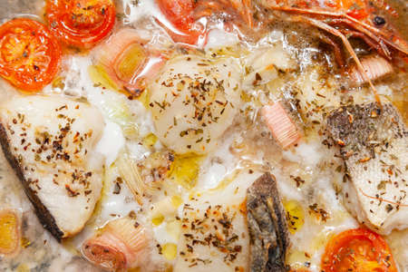 Detailed shot of a recipe for baked cod with vegetables. There are fish, shrimp, cherry tomatoes, leek, onion, garlic, aromatic herbs, olive oil and white wine. It is ready to eat.
