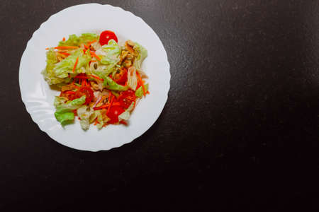 There is a salad plate in the upper left corner of the image. The ingredients are: lettuce, cherry tomato, carrot, walnuts, and pumpkin and sunflower seeds. There is room for text.