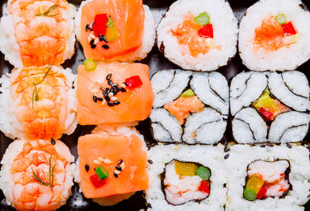 Different varieties of ready-to-eat sushi made with rice, fish, nori seaweed, shellfish, vegetables and greens. Typical dish of Japanese cuisine. Foto de archivo