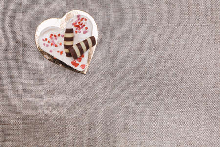 Heart-shaped cream cake served on a gold platter for Valentine's Day dessert. It is adorned with black and white chocolate eclairs and sugar hearts.