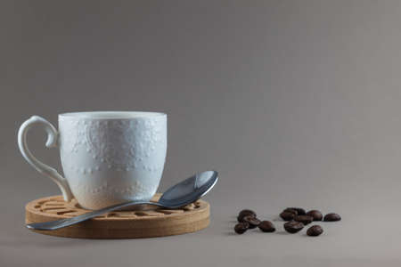 A white mug on a wooden plate next to a metal teaspoon and several coffee beans isolated on a gray background. Foto de archivo