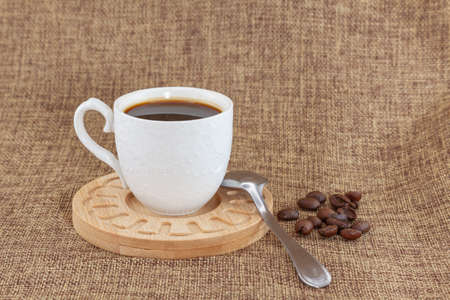 On a wooden plate there is a white cup with coffee and a metal spoon. They are placed on a sackcloth and there are a handful of coffee beans on the right side. It is seen from the front. Foto de archivo