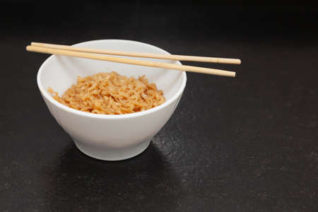 A kitchen bowl with ready-to-eat Chinese noodles. On the bowl are some oriental chopsticks. It is placed on a black granite bench in a kitchen and is viewed from the front.