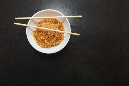 A kitchen bowl with ready-to-eat Chinese noodles. On the bowl are some oriental chopsticks. It is set on a black granite bench in a kitchen and viewed from above. Foto de archivo