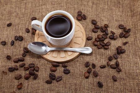 On a wooden plate there is a white cup with coffee and a metal spoon. They are placed on a sackcloth and there are coffee beans scattered around. It is seen from above.