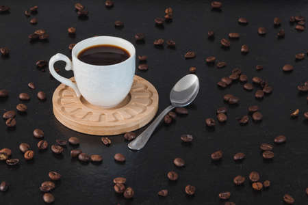 A white cup with coffee on a wooden plate, with a metal spoon on a black granite bench and many coffee beans around it.