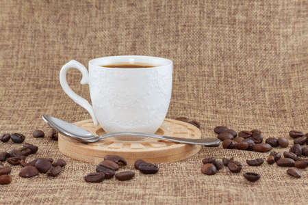On a wooden plate there is a white cup with coffee and a metal spoon. They are placed on a sackcloth and there are several coffee beans scattered around. It is seen from the front.