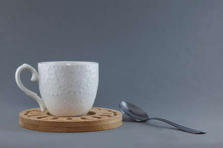A white mug on a wooden plate next to a metal teaspoon isolated on a gray background.