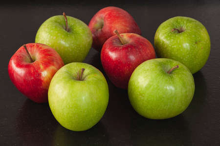 Several apples, some of them are green and some of them are red. They are on a black granite bench in a kitchen.